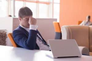frustrated businessman dejected with laptop