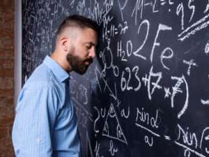 man banging head against big blackboard containing mathematical equation